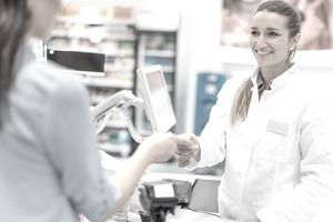 Woman paying for prescription with health insurance
