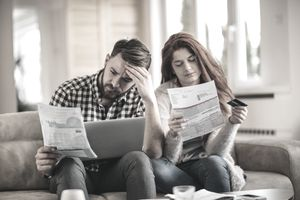 Worried couple looking at bills considering taking a title loan.