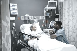 Nurse Talking to Patient in Hospital Bed