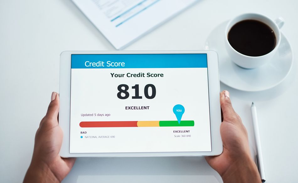 woman's hands holding a tablet with excellent credit score on screen