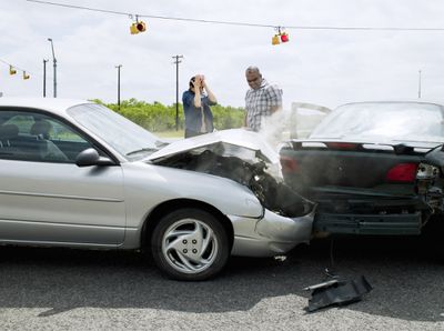 Two frustrated drivers assess the scene after a severe fender bender