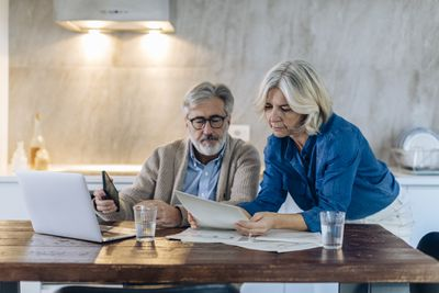 Older couple sitting at table working on a laptop