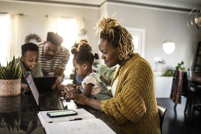 Mother working from home while holding toddler, family in backgroun