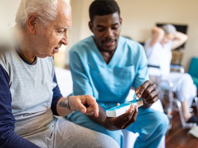 Young male nurse helps elderly patient with weekly pill planner