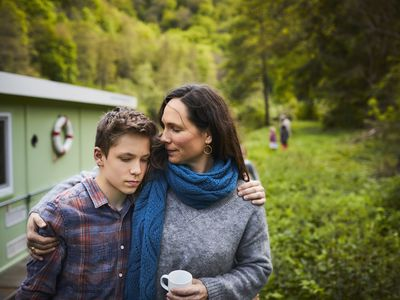 Mother consoles sad son as they walk outdoors