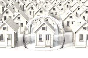 Several small wooden house models with one inside of a protective bubble of homeowner's insurance.