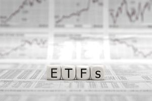 Block letters spelling ETFs on top of stock market reports and graphs.