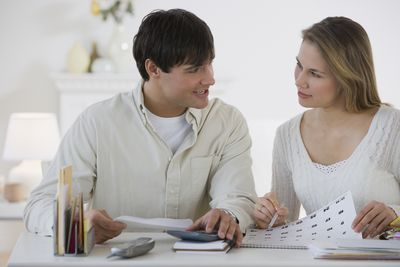 Young couple paying bills side by side at a home desk