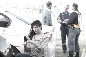 A woman holding a smartphone photographs damage to a car while in the background a man and two first responders have a discussion.