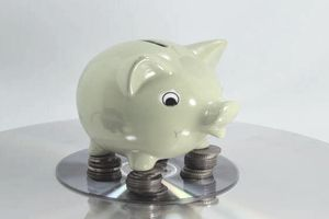 Piggy bank standing on top of stacked coins and a CD, showing the choices in putting your money in a savings account or CD