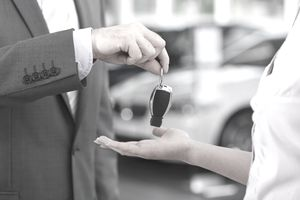 At the car dealer, salesman handing over car key to client.