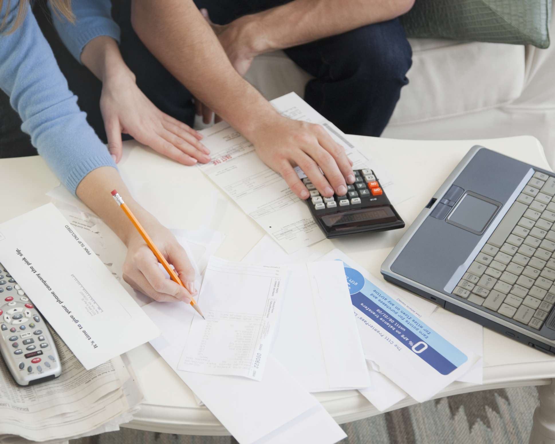 Hands of a couple doing paperwork and going over finances at a computer