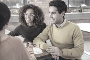 A couple discusses refinancing options with a potential lender