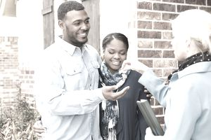 young adult couple receives a house key to their first home from their realtor.