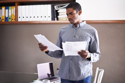 A businessman looks over some paperwork in his home office
