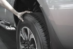 Male Hand Resting on New Tire on Car