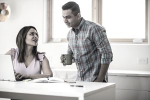 Husband and wife using laptop in kitchen