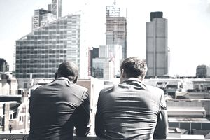 Two businessmen on rooftop overlooking city with building cranes considering FFO of their REIT investments