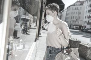 Woman wearing protective face mask doing window shopping while standing on street in city