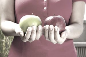 A woman holding a red apple in one hand and a green apple in the other, representing comparing pension and annuity rates.
