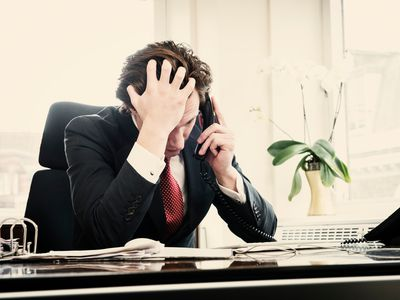 Frustrated investor on telephone, head in hands