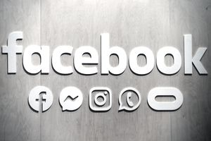 Facebook logo on wall with the company's other properties including WhatsApp, Instagram and Oculus VR.