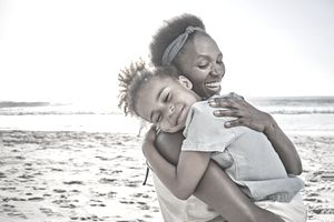 Mother hugging daughter on beach