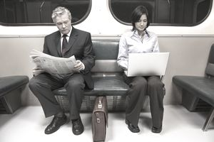 2 people on subway with newspaper and laptop