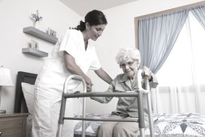 Nursing home employee helping an elderly woman