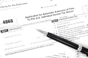 Closeup of a pen sitting atop IRS Form 4868, Application for Extension