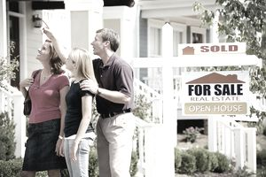 """Parents and a teenager looking up at a house with a """"for sale"""" sign"""