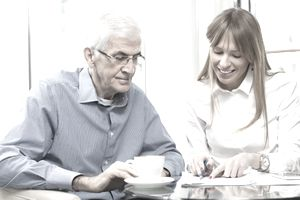 Woman advising an elderly man on paperwork