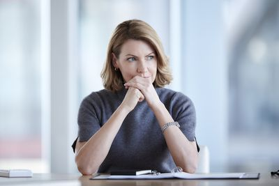 woman thinking at table with binder