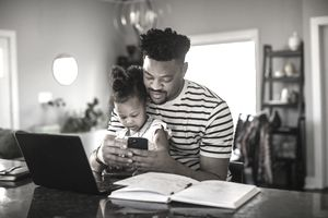Man using smartphone and laptop holds toddler daughter on lap