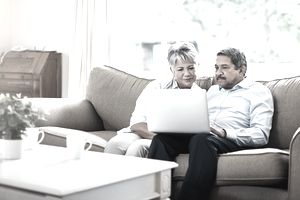 Older couple with laptop on couch