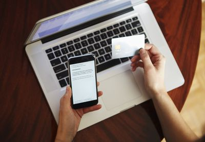 Hands holding iPhone and debit card in front of a computer