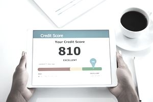 "A person holding a tablet with an ""excellent"" credit score displayed"