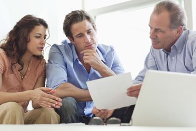 Adviser business man showing contract paper to young couple.