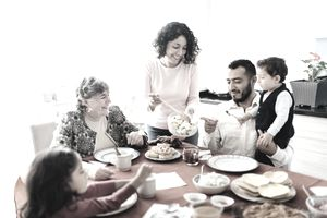 A family sits around a red table. A woman in a pink shirt dishes our food to an adult man, elderly woman, a small girl, and a small boy.