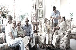 Health aide socializing with diverse group of residents in an assiste living facility