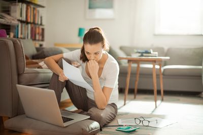 concerned woman holding paperwork and looking at laptop, seated on her living room floor