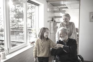 Grandmother pushing grandfather in a wheelchair with grandchild