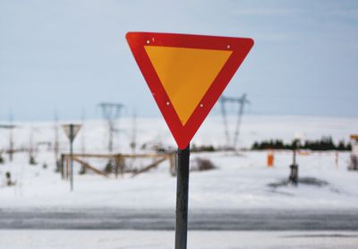 Red and yellow triangular road sign, symbolizing the need for caution