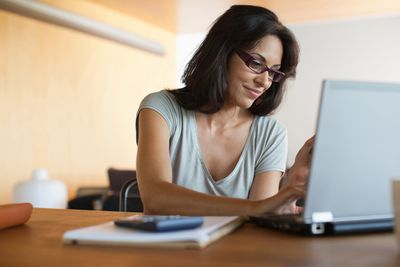 A woman uses a laptop and a calculator.