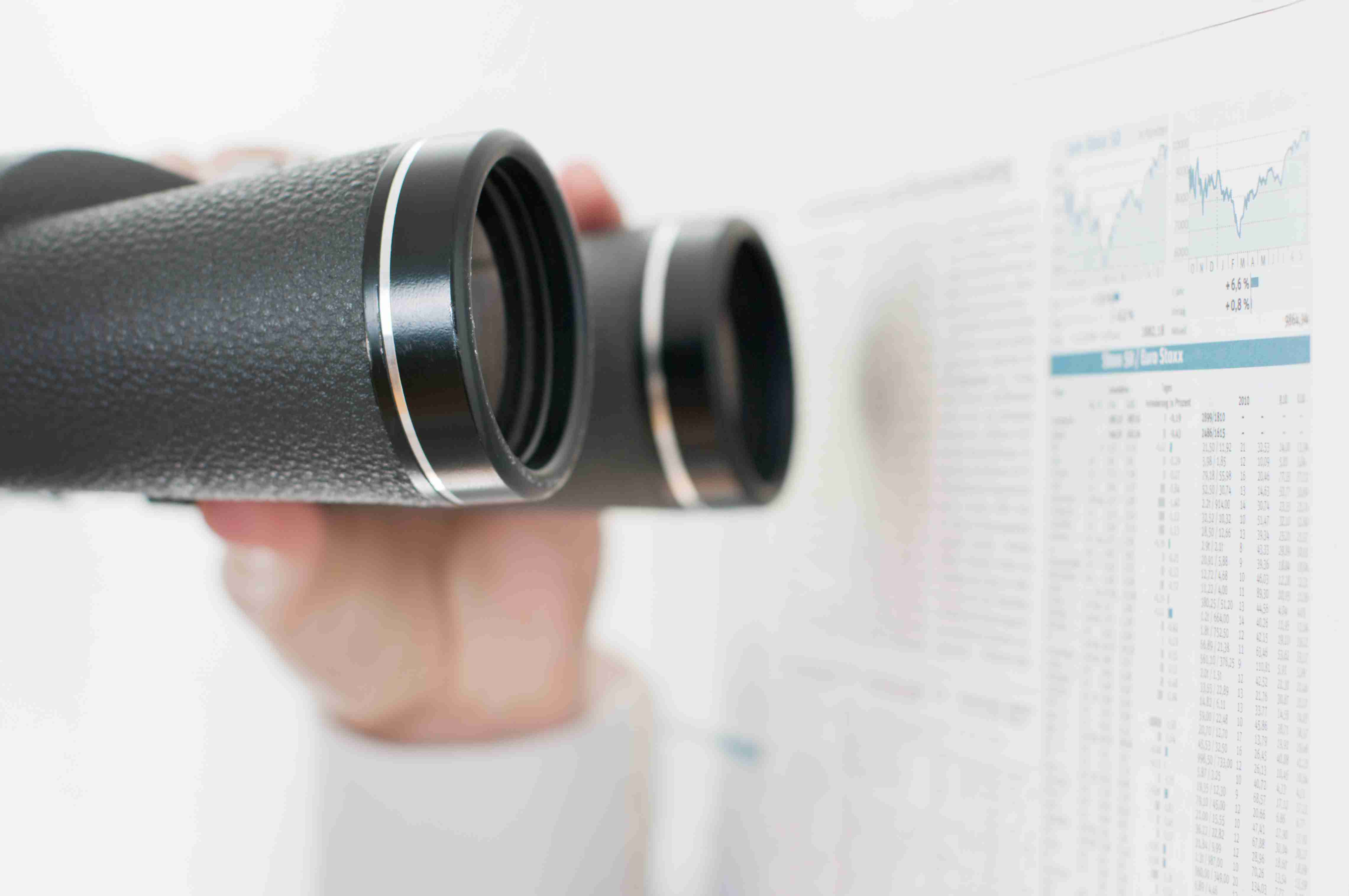 Binoculars peering into financial charts to see how benefit choices turned out