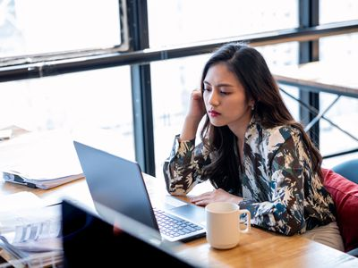Young businesswoman drinking coffee consults laptop in office