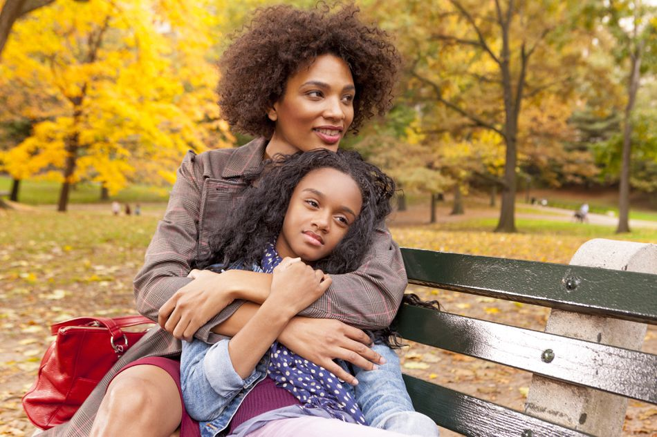 Mother and daughter sitting on park bench in Fall