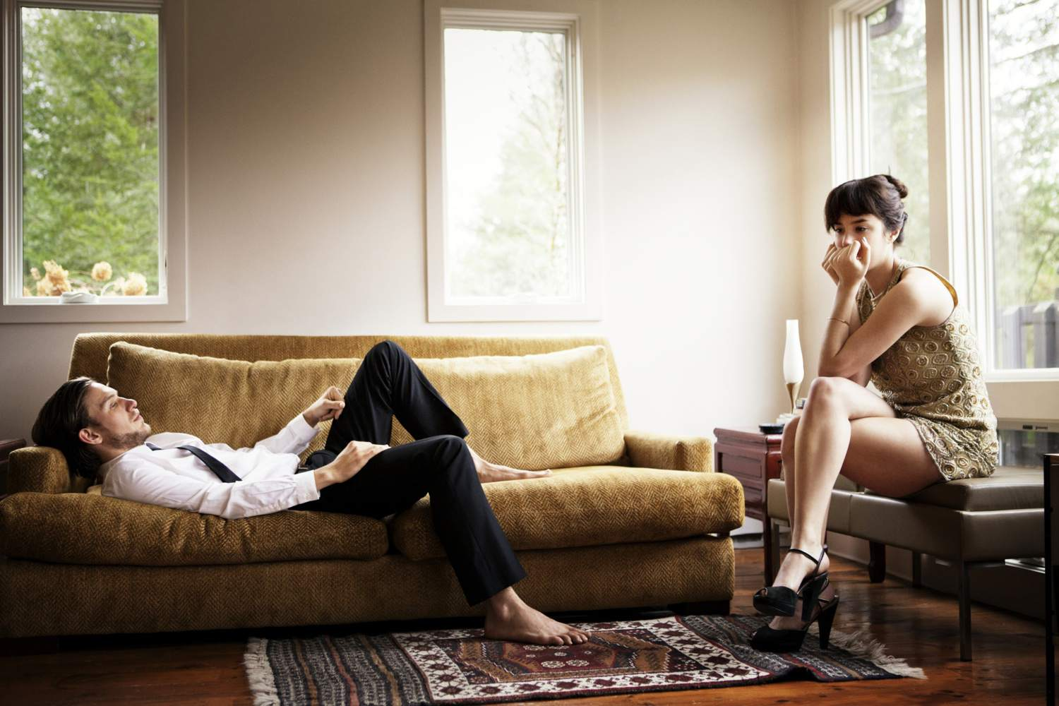 Couple looking tense and distant in a living room
