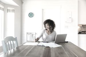 A woman sits at her dining room table with laptop, preparing to write a check