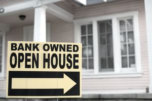 """Bank-owned open house"" sign in front of a home"